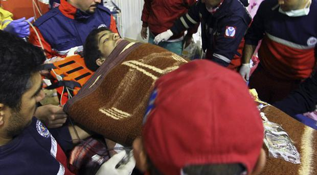 Rescuers tend Ferhat Tokay, 13, after he was pulled from the rubble of a collapsed building (AP)