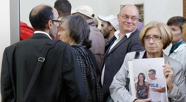 Relatives of victims arrive at court for the trial of several defendants accused of a bomb attack on a cafe which killed 17 people (AP)