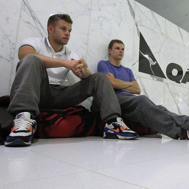 Passengers sit on the floor at the Qantas check-in counter at Sydney Airport (AP)