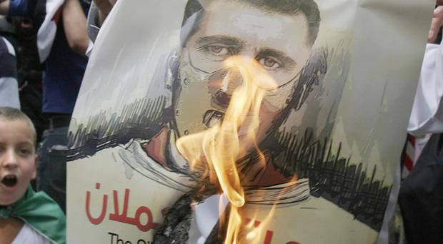 A protester burns a poster of Syrian president Bashar Assad during a demonstration in Cairo, Egypt (AP)