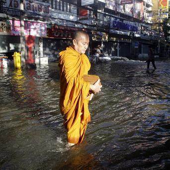 A Thai Buddhist monk wade through floodwaters in Bangkok, Thailand (AP)