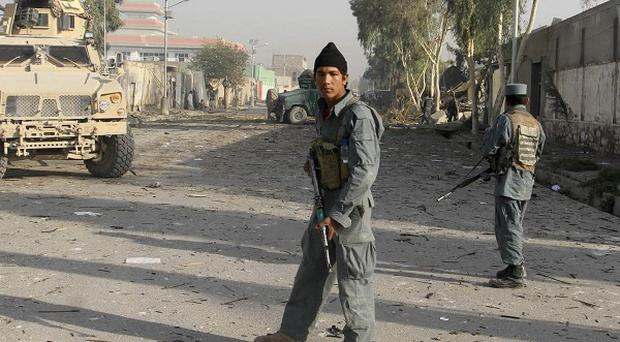 Afghan policemen gather at the site of a suicide bomb attack, in Kandahar, Afghanistan (AP)