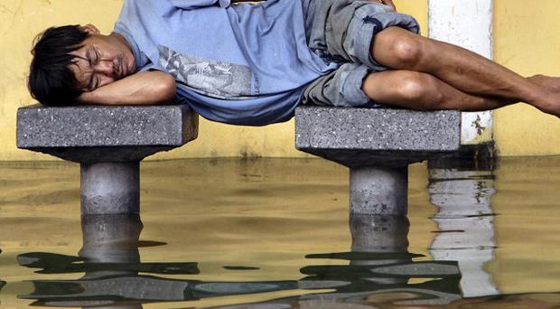 A man gets some rest at a flooded bus stop in Bangkok (AP)