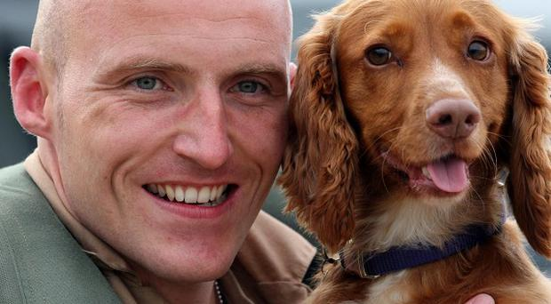 Tornado Pilot Flight Lieutenant Steve Morris from 9 Squadron holds his dog Jezebel, at RAF Marham, King's Lynn, after returning from service in Libya