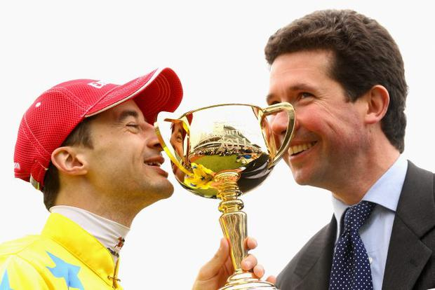 Wizards of Oz: Jockey Christophe Lemaire (left) and trainer Mikel Delzangles kiss the Melbourne Cup after Dunaden's win yesterday