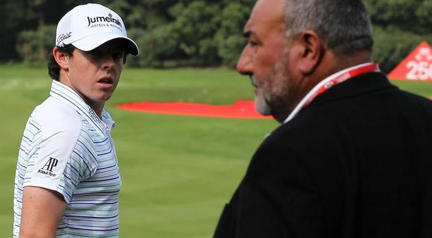 Face-to face: Rory McIlroy waits on the practice ground near his ex-manager Chubby Chandler in Shanghai yesterday