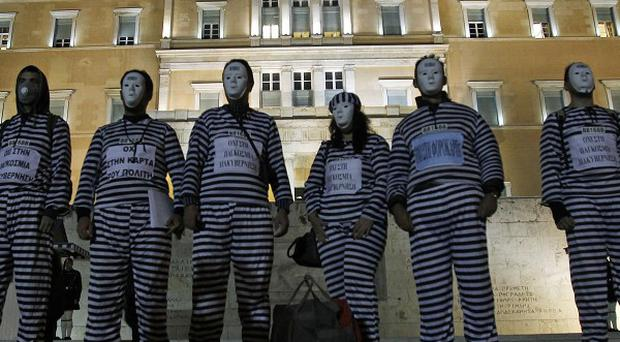Protesters dressed as prisoners stand outside the Greek parliament in Athens (AP)