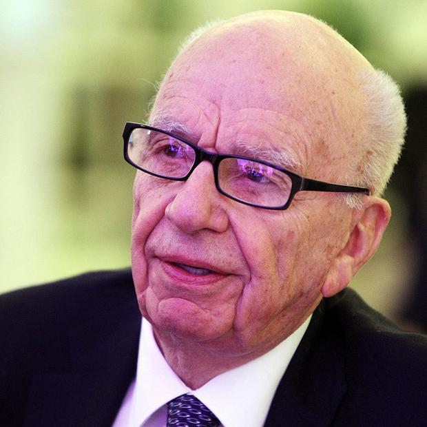 Rupert Murdoch's News Corp saw its net income fall due to the News Of The World hacking scandal
