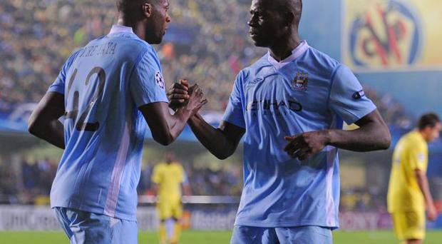 City delight: Yaya Toure celebrates scoring with Mario Balotelli last night