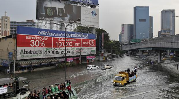 Thai residents are transported on trucks through a flooded street in Bangkok (AP)