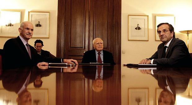 Prime Minister George Papandreou, Greek President Karolos Papoulias and opposition leader Antonis Samaras hold crisis talks (AP)