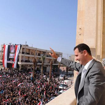 Syrian President Bashar Assad waves to his supporters in Raqqa (AP)