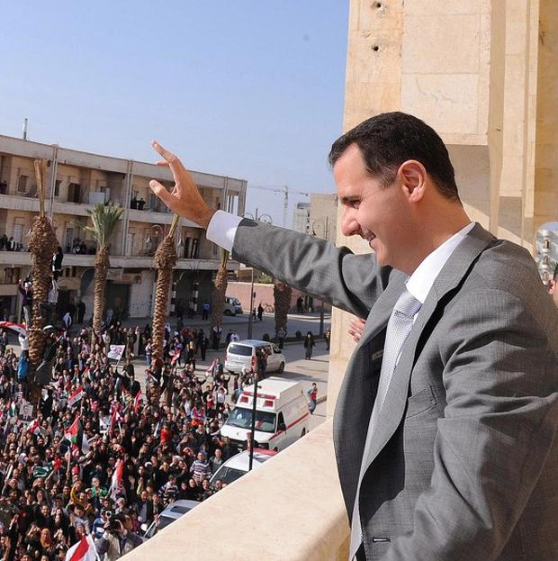 Syria's President Bashar Assad waves to his supporters after prayers in the northern town of Raqqa (AP)