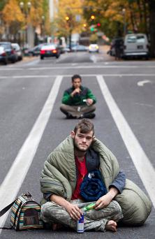PORTLAND - NOVEMBER 13: Protesters sit in the middle of a road in defiance of police instructions near the Occupy Portland encampment November 13, 2011 in Portland, Oregon. Portland police have reclaimed the two parks in which occupiers have been camping after a night of brinksmanship with protesting crowds of several thousands. (Photo by Natalie Behring/Getty Images)