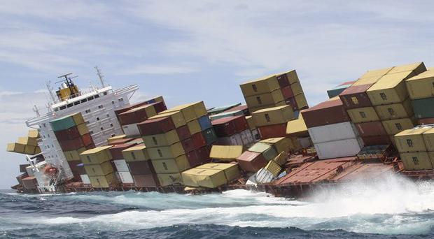 A swell buffets the hull of the cargo ship Rena that was grounded on a reef off Tauranga, New Zealand (AP)