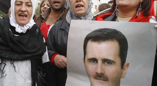 Pro-Syrian regime protesters demonstrate outside the Syrian foreign ministry in Damascus (AP)
