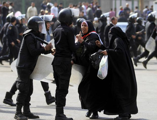 A female protester gestures as she argues with Egyptian riot police officers in Tahrir Square in Cairo, Egypt, Saturday, Nov. 19, 2011. Egyptian riot police beat protesters and dismantled a small tent city set up to commemorate revolutionary martyrs in Cairo's Tahrir Square on Saturday. (AP Photo/Khalil Hamra)