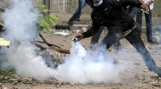 A protester throws a tear gas grenade back at Egyptian riot police near the interior ministry in downtown cairo, Egypt, Sunday, Nov. 20, 2011. Firing tear gas and rubber bullets, Egyptian riot police on Sunday clashed for a second day with thousands of rock-throwing protesters demanding that the ruling military quickly announce a date to hand over power to an elected government. The police battled an estimated 5,000 protesters in and around central Cairo's Tahrir Square, birthplace of the 18-day uprising that toppled authoritarian leader Hosni Mubarak in February. (AP Photo/Khalil Hamra)