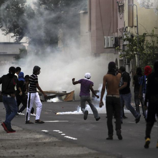 Tear gas fills a street of anti-government protesters in Sitra, Bahrain, where clashes erupted ahead of a report into the country's unrest (AP)