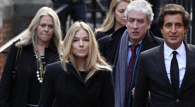 LONDON, ENGLAND - NOVEMBER 24: Actress Sienna Miller (2nd L) and and David Sherborne QC (R) arrive to give evidence to the Leveson Inquiry at The Royal Courts of Justice on November 24, 2011 in London, England. The inquiry is being lead by Lord Justice Leveson and is looking into the culture, practice and ethics of the press in the United Kingdom. The inquiry, which will take evidence from interested parties and may take a year or more to complete, comes in the wake of the phone hacking scandal that saw the closure of The News of The World newspaper. (Photo by Oli Scarff/Getty Images)