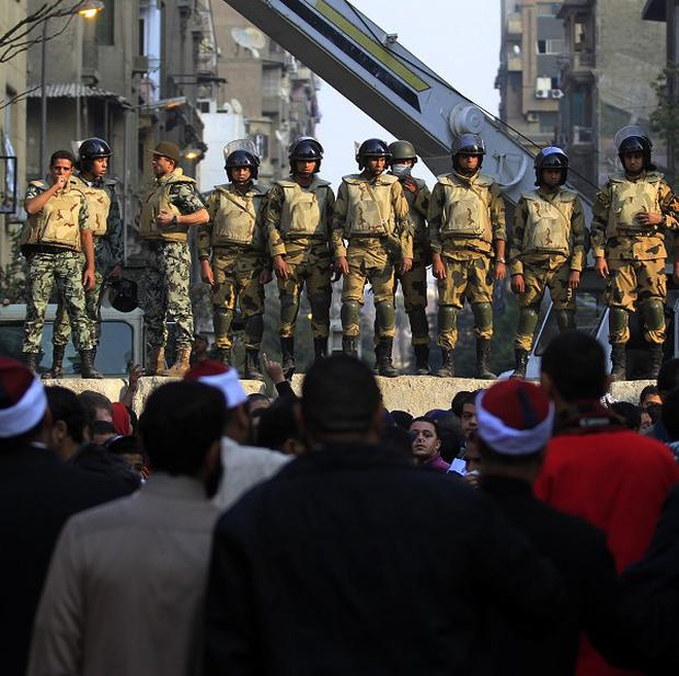 Soldiers have built barricades to separate protesters and police on side streets leading from Tahrir Square (AP)