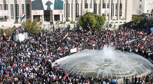 Supporters of the Syrian government protest against Arab League sanctions in Damascus (AP)