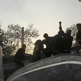 Iranian protesters chanting slogans, as they stand on the gate of the British Embassy, in Tehran (AP)