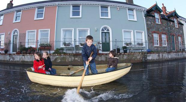 A Young boy paddles his rowing boat up the main street in Strangford village in Co Down as the heavy rain storm and high tides floodb the village, the road was closed for several hours picture Bill Smyth