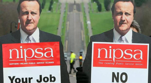 Striking workers, life size images of Prime Minister David Cameron outside Stormont Castle.