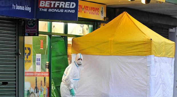 Forensic officers work at Stanley News and Wines on Kingsway, Huyton, Liverpool, where a shop worker was stabbed to death