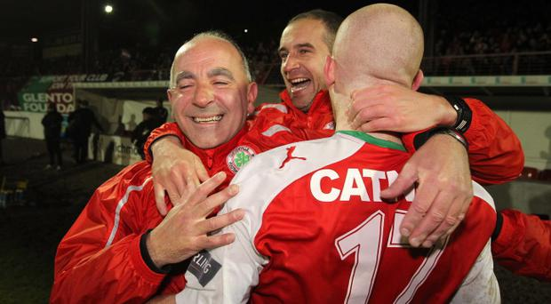 Cliftonville boss Tommy Breslin joins in the celebrations with his players after the County Antrim Shield win