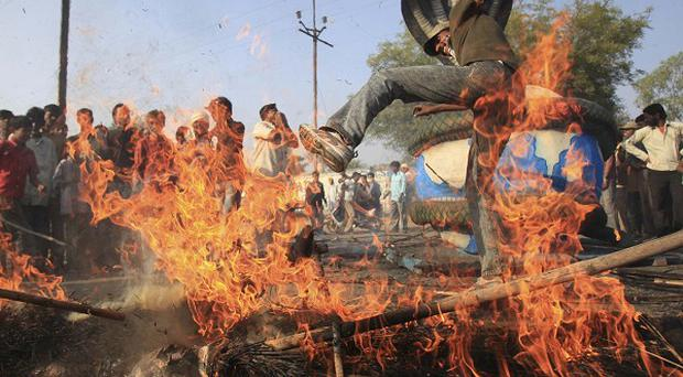 A survivor of the Bhopal disaster dances on a burning effigy of London Olympics chief Lord Coe (AP)