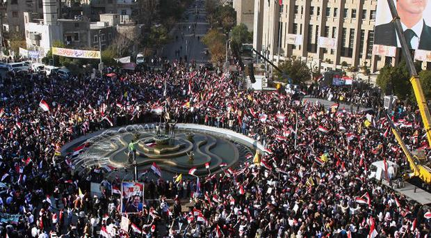 Pro-Syrian regime demonstrators gather during a protest against sanctions in Damascus (AP)