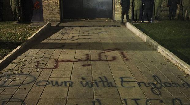 Anti-British and anti-US graffiti is written by hard-line protesters in front of the British Embassy residence in Tehran (AP)