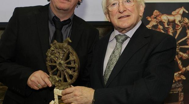 President Michael D Higgins presents Michael Collins with his trophy at the Traveller Pride Awards