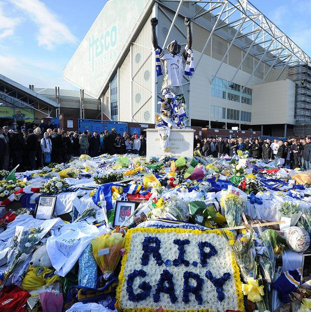 Fans stand around the shrine to Gary Speed at the Billy Bremner statue outside Leeds United's football ground