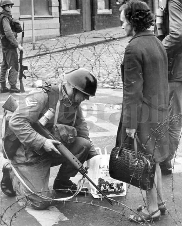 Riots : Belfast. August 1969. A woman has her message bag searched before being allowed to re-enter the sealed off area after doing her shopping. (16/8/69)