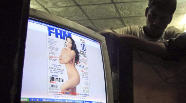 Pakistanis look at a website displaying Veena Malik's photo on the website of FHM India, at an Internet cafe in Karachi, Pakistan, Saturday, Dec. 3, 2011.