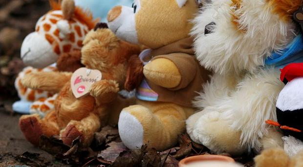 Lit candles, soft toys and good will messages are left at the scene of a vigil in Gravesend