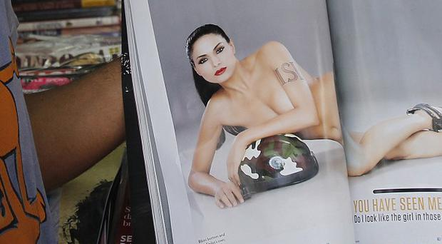 A man displays a copy of FHM India that actress Veena Malik is suing over, claiming photos were doctored to make her appear nude (AP)