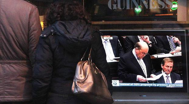 A couple stop to watch a television outside a pub in Dublin as Finance Minister Michael Noonan delivers his Budget