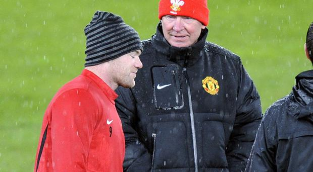 Manchester United coach Alex Ferguson talks with player Wayne Rooney, during a training session at the St. Jakob-Park stadium in Basel, Switzerland, Tuesday, Dec. 6, 2011