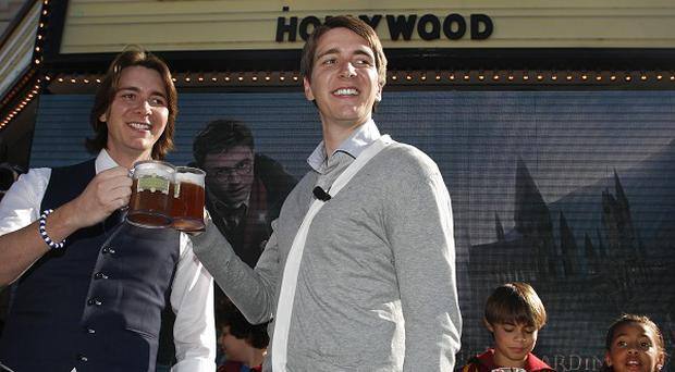 Harry Potter cast members James and Oliver Phelps make a butterbeer toast at the announcement