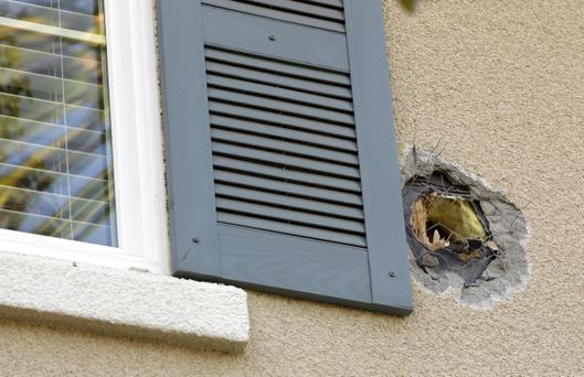 A hole near the master bedroom window of a Dublin, Calif. home marks the exit point of an errant cannonball fired during a filming of an episode of the Discovery Channel's