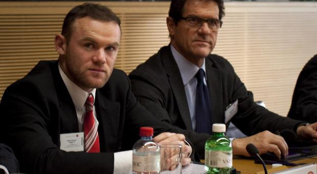 Manchester United's Wayne Rooney, left, and England coach Fabio Capello are seen before an appeal against Rooney's three-match ban which excludes him from England's 2012 European Championship group-stage matches at the UEFA headquarters in Nyon, Switzerland, Thursday, Dec 8, 2011
