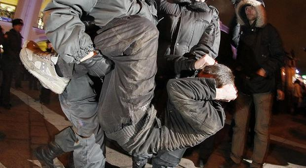 Riot police detain a protester during a rally over alleged election fraud in downtown St Petersburg, Russia (AP)