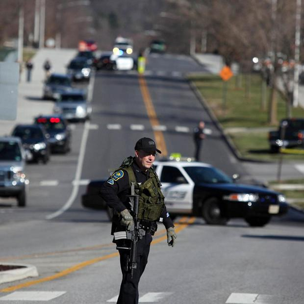 Police officers block a road on the Virginia Tech campus after a gunman killed a police officer (AP)