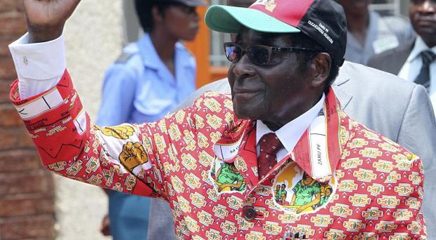 Zimbabwean president Robert Mugabe greets the crowd upon his arrival for the official opening of the Zanu PF Congress in Bulawayo (AP)