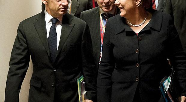 French president Nicolas Sarkozy and German chancellor Angela Merkel talk as they head to a working dinner at the EU summit (AP)