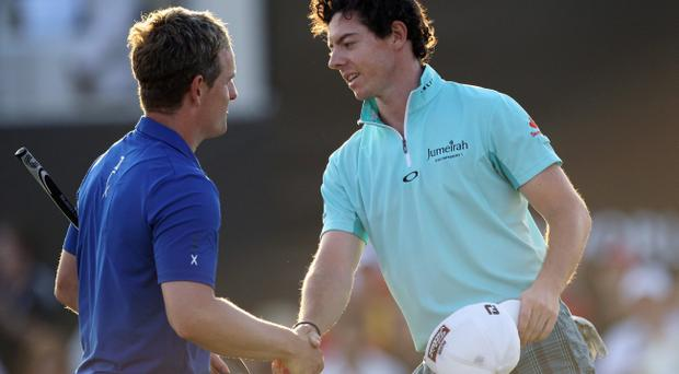 DUBAI, UNITED ARAB EMIRATES - DECEMBER 08: Rory McIlroy of Northern Ireland (right) shakes hands with Luke Donald of England on the 18th green during the first round of the Dubai World Championship on the Earth Course, Jumeirah Golf Estates on December 8, 2011 in Dubai, United Arab Emirates. (Photo by Andrew Redington/Getty Images)
